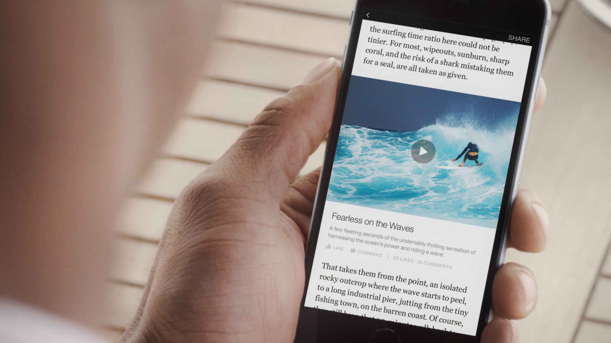 Still of a guy holding a phone, reading an article on surfing.