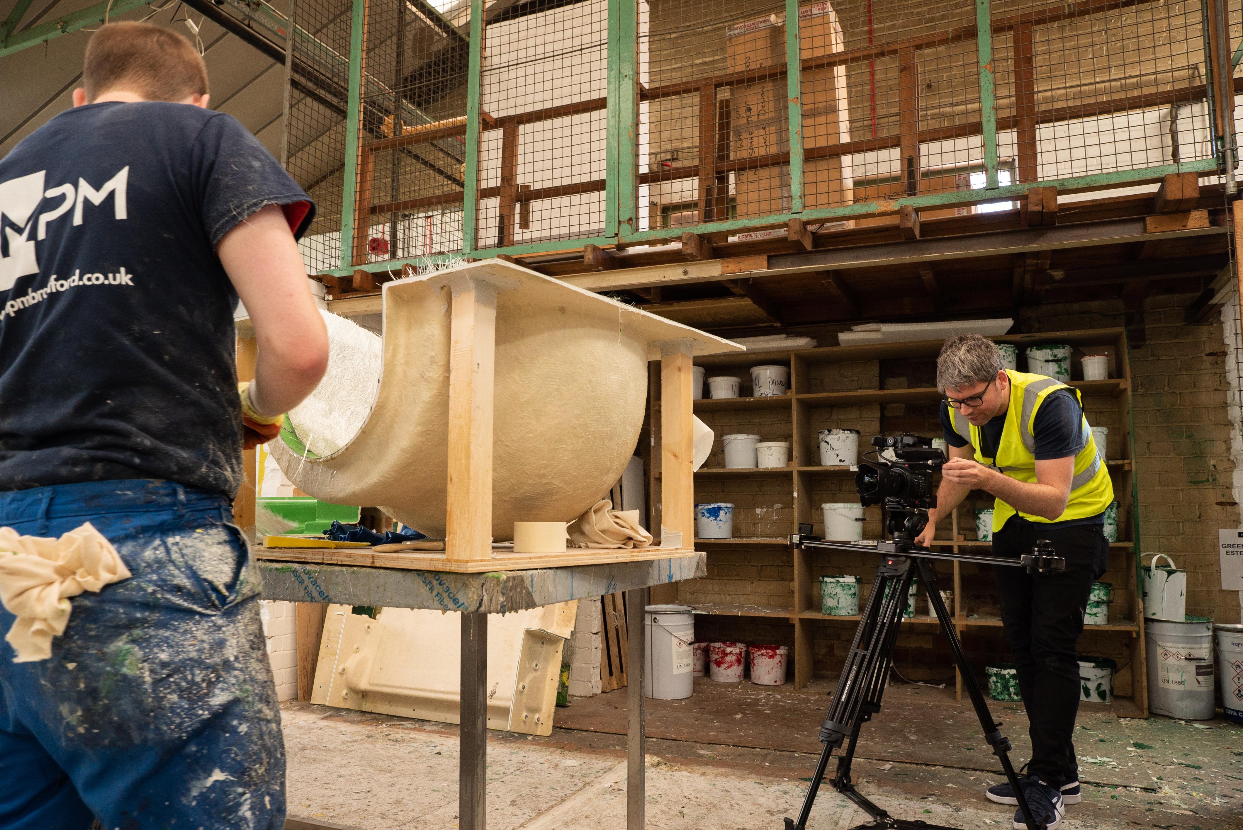 Camera man filming workman making a fibreglass mould