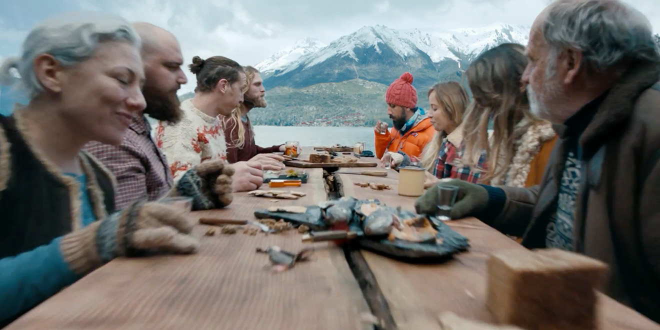 People sat around a trestle table in Iceland eating food and socialising